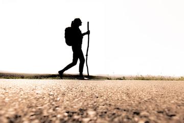 Silhouette einer Frau mit Rucksack auf einem Pilgerweg