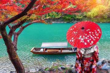 Keuken foto achterwand Rood Asian woman wear Kimono and watch The leaves change color. Boatman on the Katsura River on both sides is full of beautiful colorful trees.