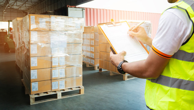 warehouse worker hand holding clipboard inspecting checklist details of cargo shipment, goods pallets for loading with a truck container at dock warehouse. freight industry delivery logistics.