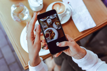 A girl takes photos of delicious food on the phone.