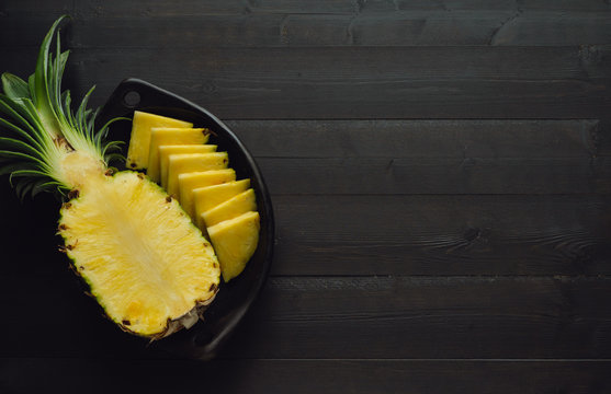 Pineapple cut in black bowl on dark wooden background. Copy space.