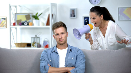 Woman with megaphone shouting on man at home, unsuccessful marriage, conflict