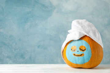 In de dag Spa Pumpkin with facial mask and towel on wooden background, copy space