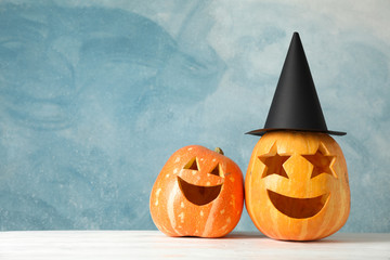 Funny pumpkins on white wooden background, space for text