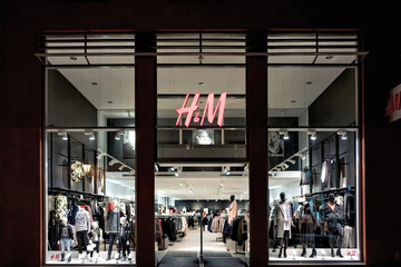 WISMAR, GERMANY - November 9, 2016: entrance of a H&M branch in the dark. H&M is a Swedish multinational clothing-retail company and is ranked the second largest global clothing retailer.