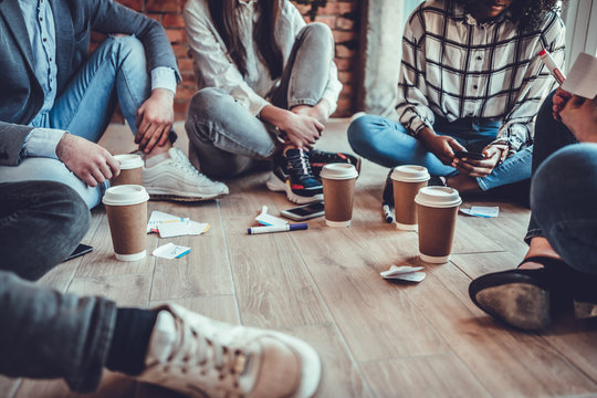 young business people in casual clothes are discussing work, drinking coffee and smiling while sitting on the floor in office