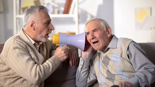 Senior man shouting bullhorn to deaf friend, old aged health, deafness treatment