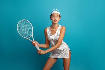 girl tennis player in a white dress in a sun visor with a tennis racket. Blue background. Studio photography.