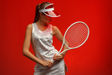 girl tennis player in a white dress in a sun visor with a tennis racket. Red background. Studio photography.