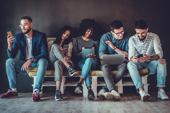 Group of happy young people sitting on sofa and using digital tablet and laptop