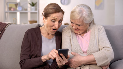 Happy aged friends watching online video on smartphone, modern technology, app