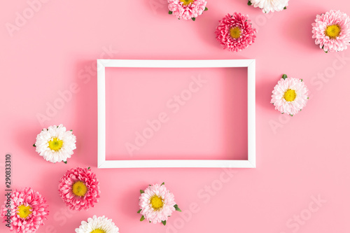 Beautiful flowers composition. White photo frame, pink flowers on pastel pink background. Valentines Day, Happy Women's Day, Mother's day. Flat lay, top view, copy space