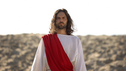 Jesus looking at camera, preaching Christian faith in desert, soul salvation
