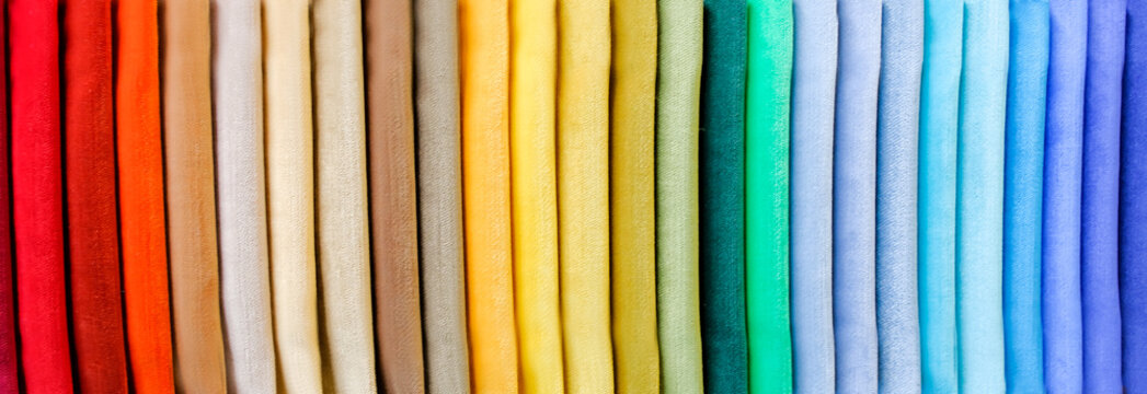 Rainbow clothes background. Pile of bright folded clothes.