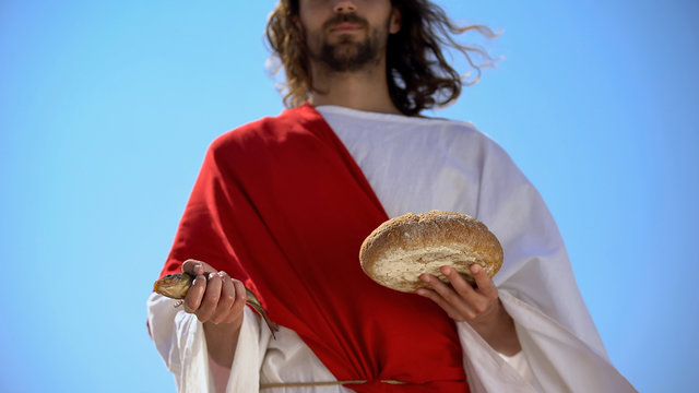 Man in robe holding fish and bread, charity concept to feed hungry, generosity