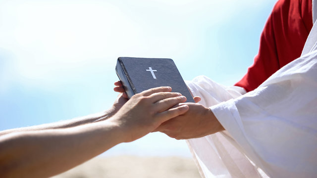 Preacher in robe passing bible to male hands, spreading religious teachings
