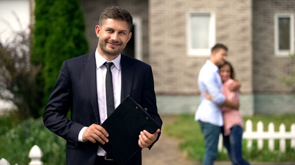 Smiling broker standing with documents, happy family hugging near their new home