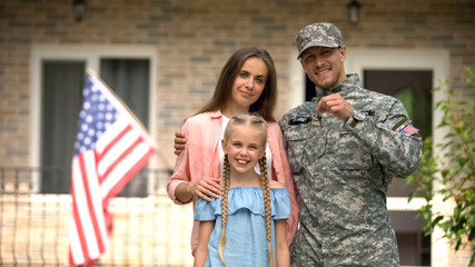 US military man with family showing keys from house, benefits in crediting