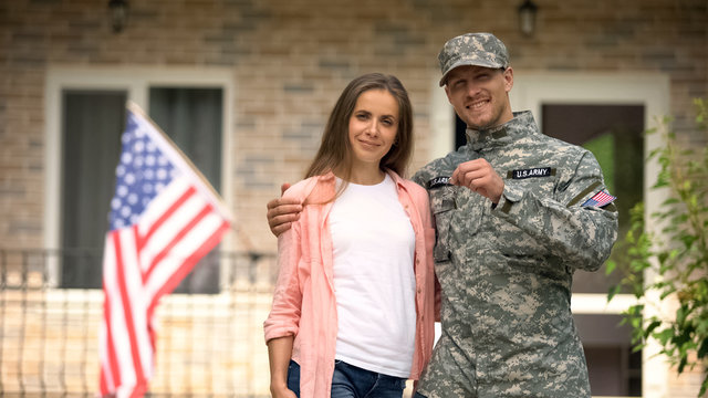 Soldier and wife showing keys from new house, government social insurance