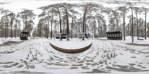 Winter full spherical seamless hdri panorama 360 degrees angle view on pedestrian road in snowy park with gray pale sky near arches and benches in equirectangular projection. VR AR content