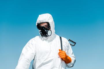 exterminator in white uniform and latex glove holding spray