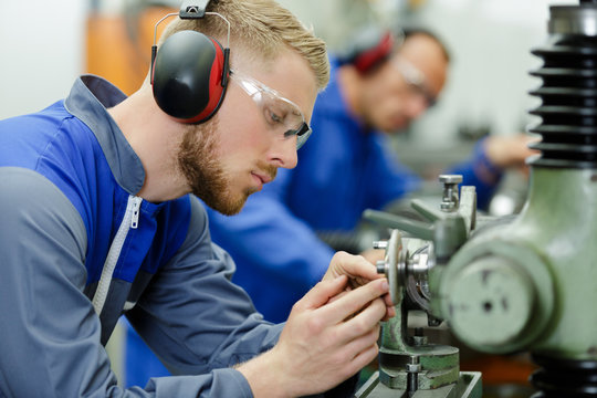 young man with ear protection in factory
