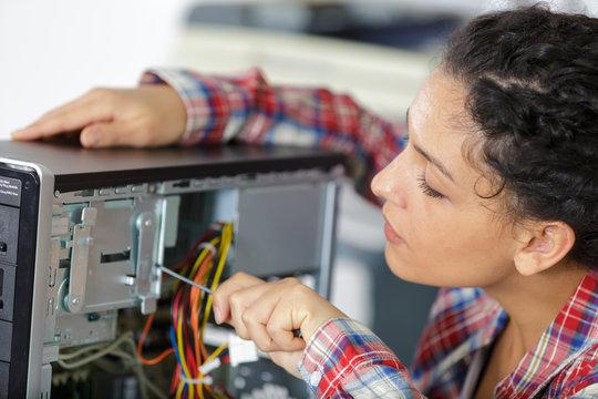 young woman fixing a desktop computer