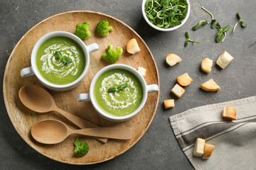 Flat lay composition with bowls of broccoli cream soup on grey table