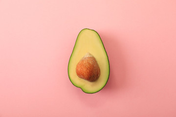Half of delicious avocado on pink background, top view