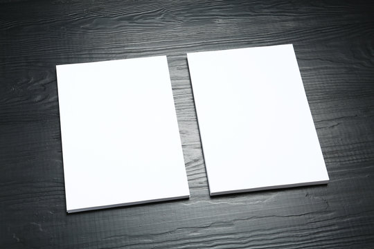 Blank paper sheets for brochure on black wooden background. Mock up