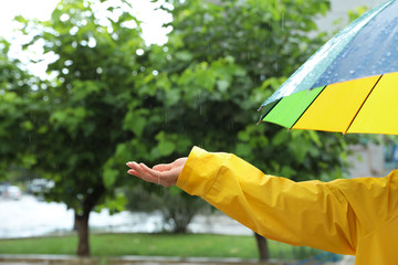 Wall Mural - Woman with colorful umbrella outdoors on rainy day, closeup