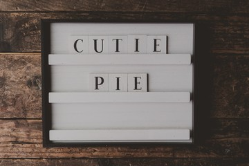 """White sign with a writing """"Cutie pie"""" on it on a wooden brown background"""