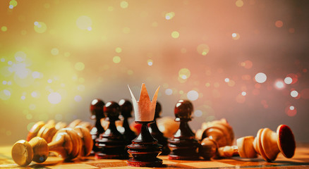 Business game, teamwork, leader and competition concept. A chess pawn with a crown on its head
