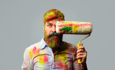 Painter man. Professional painter, decorator. Repair, building concept. Room painting job. Handsome bearded worker with paint roller. Builder worker, repairman, tradesman, handyman with paint roller.