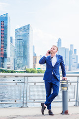 Young American Businessman with beard, talking on cell phone, traveling in New York City, wearing blue suit, white shirt, standing in business district with high buildings in Midtown of Manhattan..