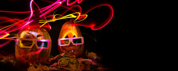 luminous pumpkins in the dark for the autumn Halloween holiday. 3D movie for Halloween. Pumpkin Head Jack in 3D glasses for the movie. Bright neon pink and blue light in the darkness of Freezelight