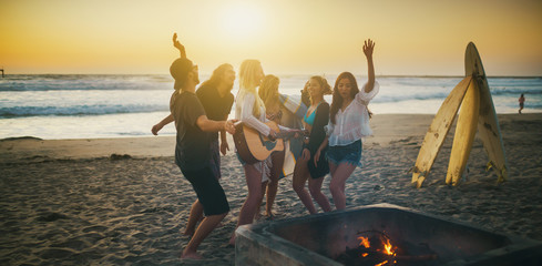 group of surfer friends at beach party dancing and playing music