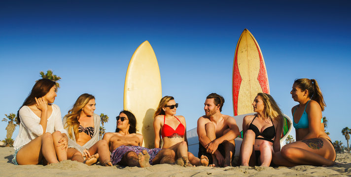 group of 7 friends sitting on beach with surfboards in california