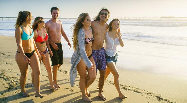 group of friends walking alongside california beach