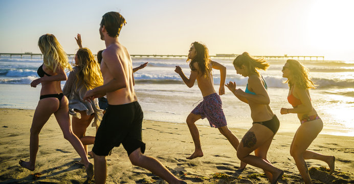group of friends running alongside beach in california