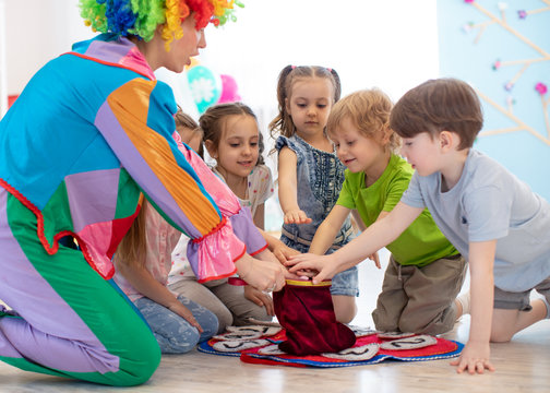 Group of happy smiling preschool kids watching at clown show indoor. Party for children.