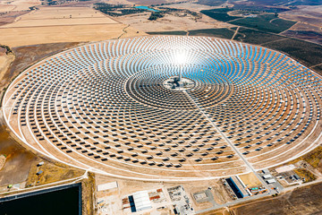 Solar panels in a large thermal circular power plant with the reflection of the sunlight in the panels. Renewable and pollution-free energy in a solar farm in Spain- aerial view with a drone - environ