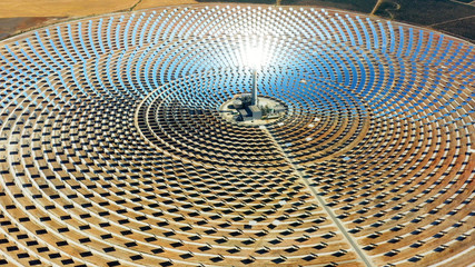 Beautiful large circular power plant of solar panels in Spain. There is the reflection of the sun in the the panels which produce renewable energy, solar energy - close-up view with a drone - environm
