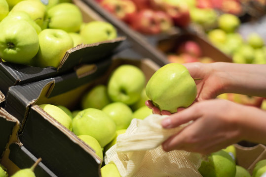 Woman chooses green apples at farmers market. Zero waste, plastic free concept. Sustainable lifestyle. Reusable cotton and mesh eco bags for shopping.