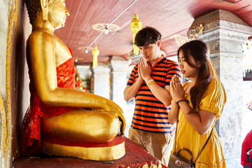 thai couple praying in front of buddha statue at Wat Phrathat Doi Suthep temple in chiang mai thailand