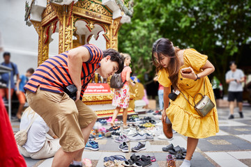 thai tourist couple removing shoes before walking into temple