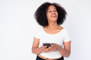 Portrait of happy young beautiful African woman thinking while using phone