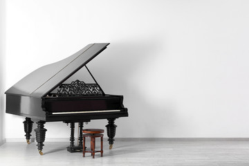 Black grand piano near white wall in empty room
