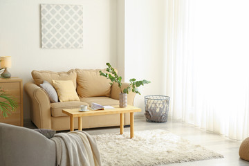 Stylish interior of room with sofa and eucalyptus branches in vase on table