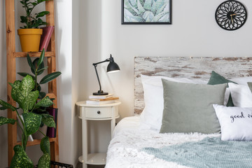 Big comfortable bed and table with lamp and plants in stylish interior of room